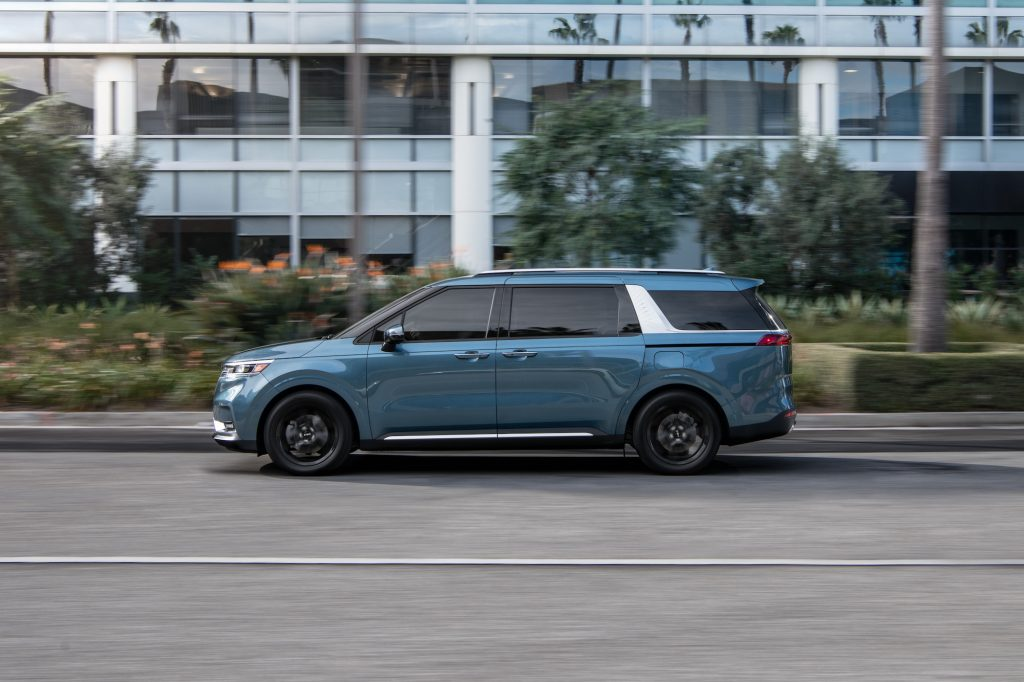 A blue 2022 Kia Carnival, which resembles an SUV and a minivan, travels on a street past palm trees and a modern building