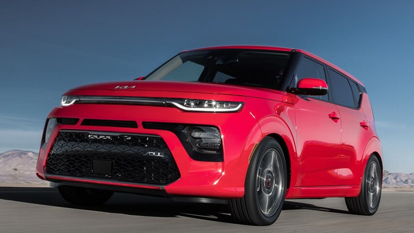 A red 2022 Kia Soul driving on a desert road