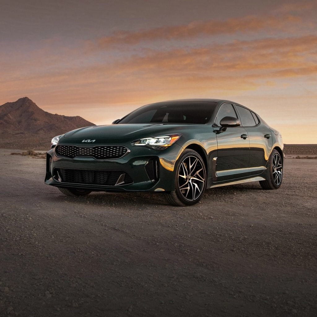 A dark colored 2022 Kia Stinger sits on a dirt road with a small hill behind it. The 2022 Kia Stinger is an IIHS Top Safety Pick+.