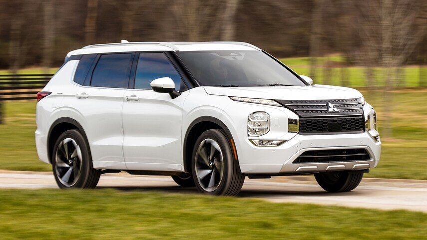 A white 2022 Mitsubishi Outlander driving through the country