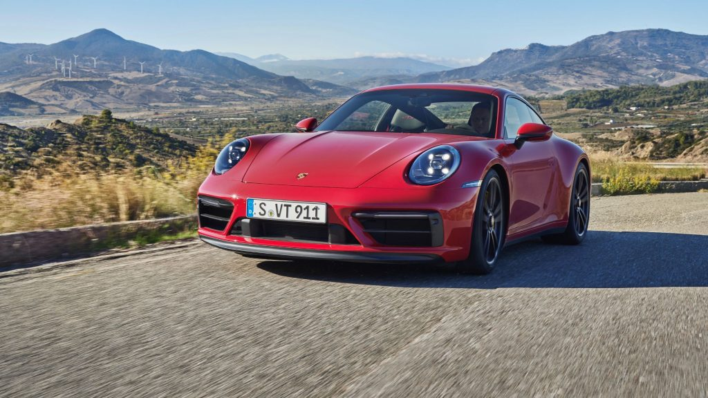 A red 2022 Porsche 911 Carrera GTS Coupe drives around a mountain road