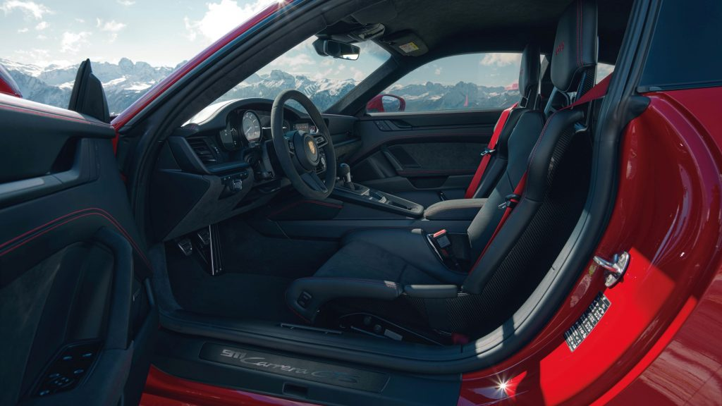 The black interior and carbon-fiber bucket seats of a red 2022 Porsche 911 Carrera GTS Coupe interior with the Lightweight Package