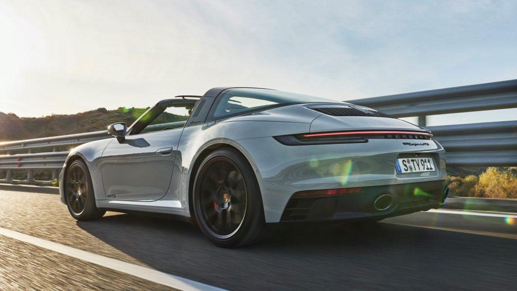The rear 3/4 view of a white 2022 Porsche 911 Targa 4 GTS driving down a mountain road