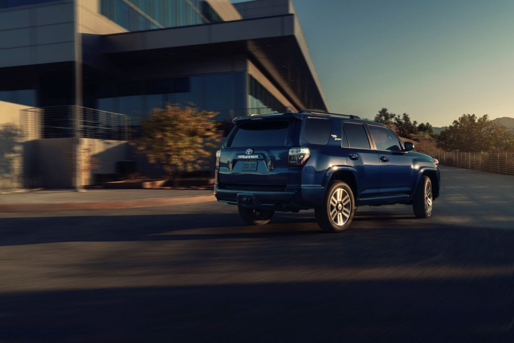 The rear 3/4 view of a dark-blue 2022 Toyota 4Runner TRD Sport driving around the corner of a building