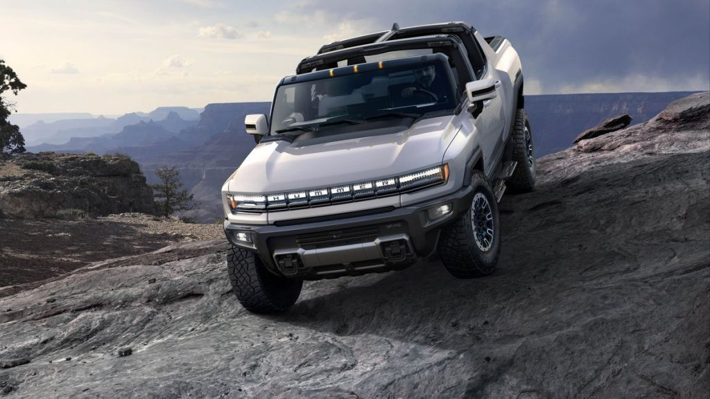The 2022 GMC Hummer EV truck driving down a large rock