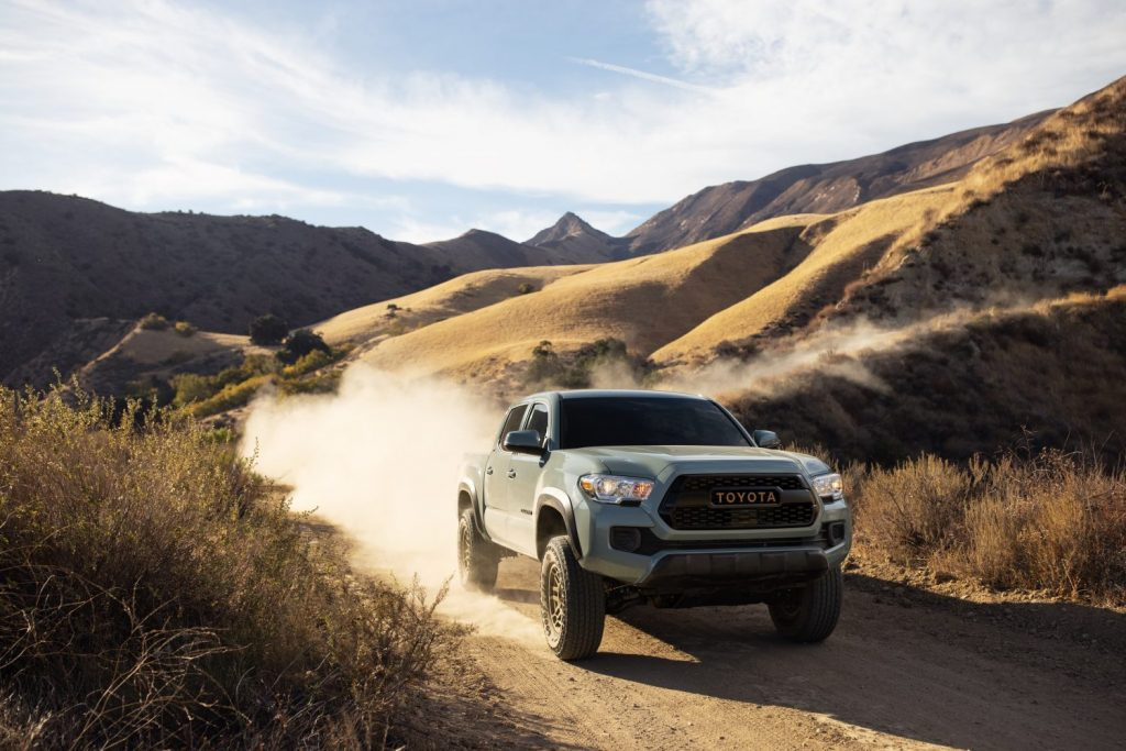 a 2022 Toyota Tacoma Trail Edition on a dusty mountain trail kicking up dirt