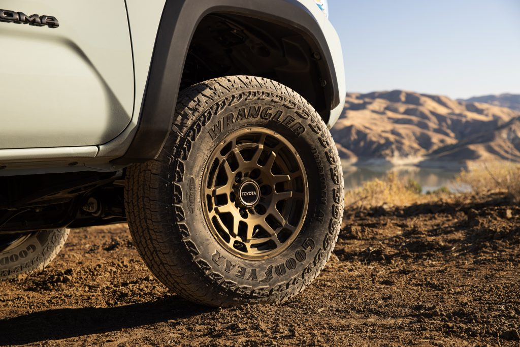 the bronze-finished wheels inside the Goodyear Wranglers of the 2022 Toyota Tacoma Trail Edition off-road pickup truck.