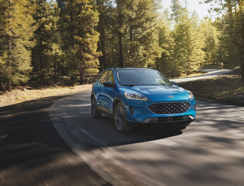 A blue 2021 Ford Escape Hybrid driving