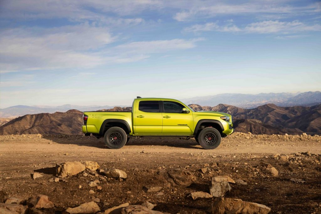side view of an electric green Toyota Tacoma TRD Pro 2022 model driving on a sandy trail