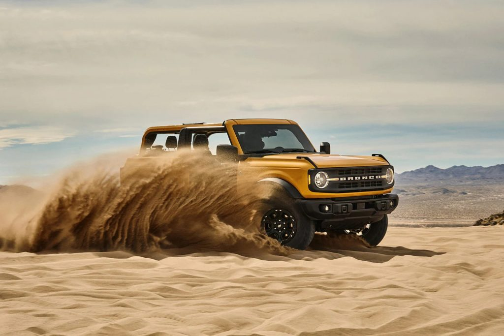 The yellow Ford Bronco plays sideways in the sand