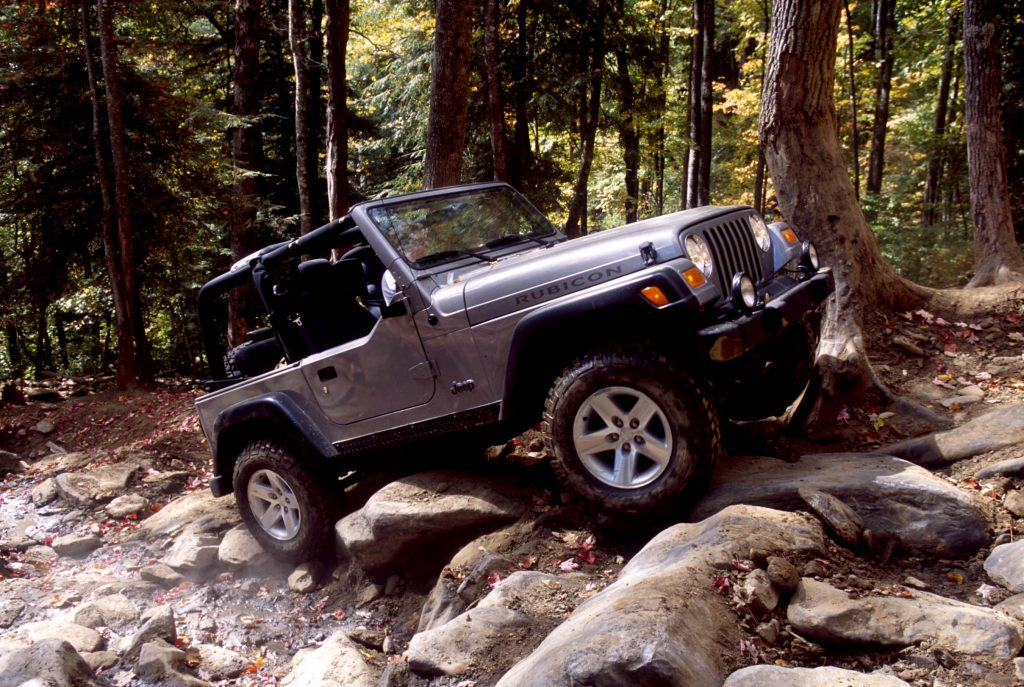 A silver Jeep Wrangler clambers up rocks on a trail