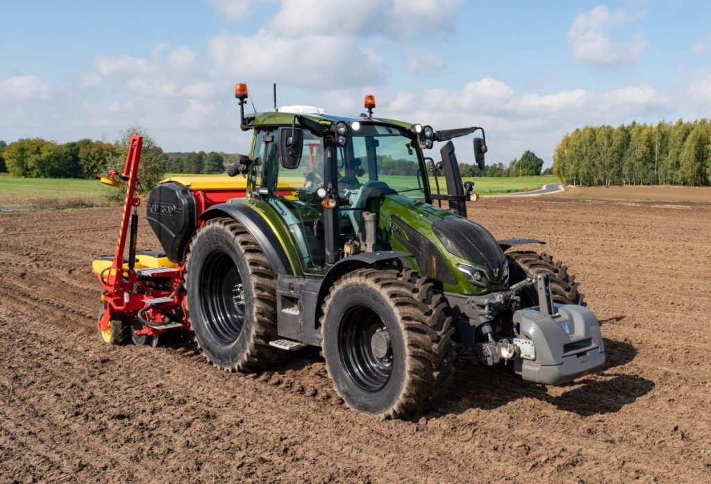 Valtra G 135 Versu utility tractor model in a crop field on a sunny day