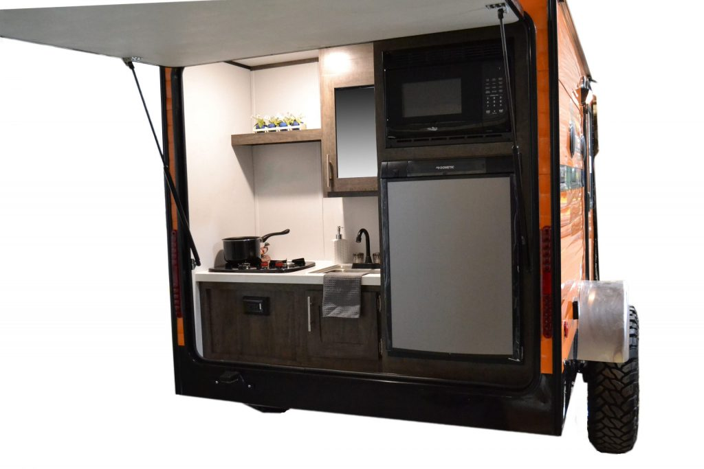 the rear of the retro RV camper trailer showing the kitchen beneath a fold out awning that doubles as a rear hatch.