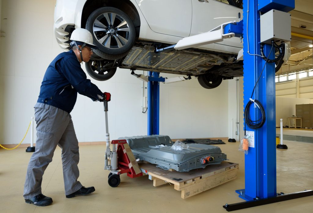 A blue-clothed 4R Energy employee moves a used battery pack from a white Nissan Leaf at a recycling facility