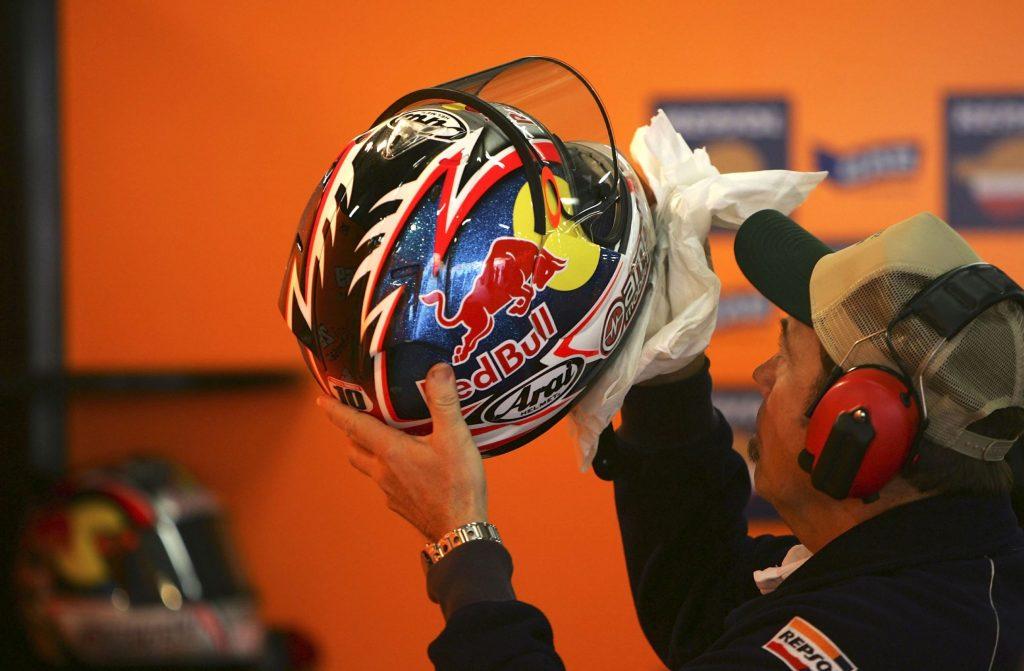 A Repsol Honda MotoGP mechanic cleaning a motorcycle helmet for Nicki Hayden at the 2006 Shanghai GP