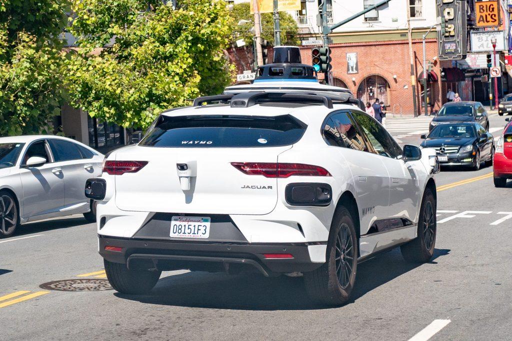 A white Waymo semi-autonomous Jaguar I-Pace car testing on the streets of San Francisco