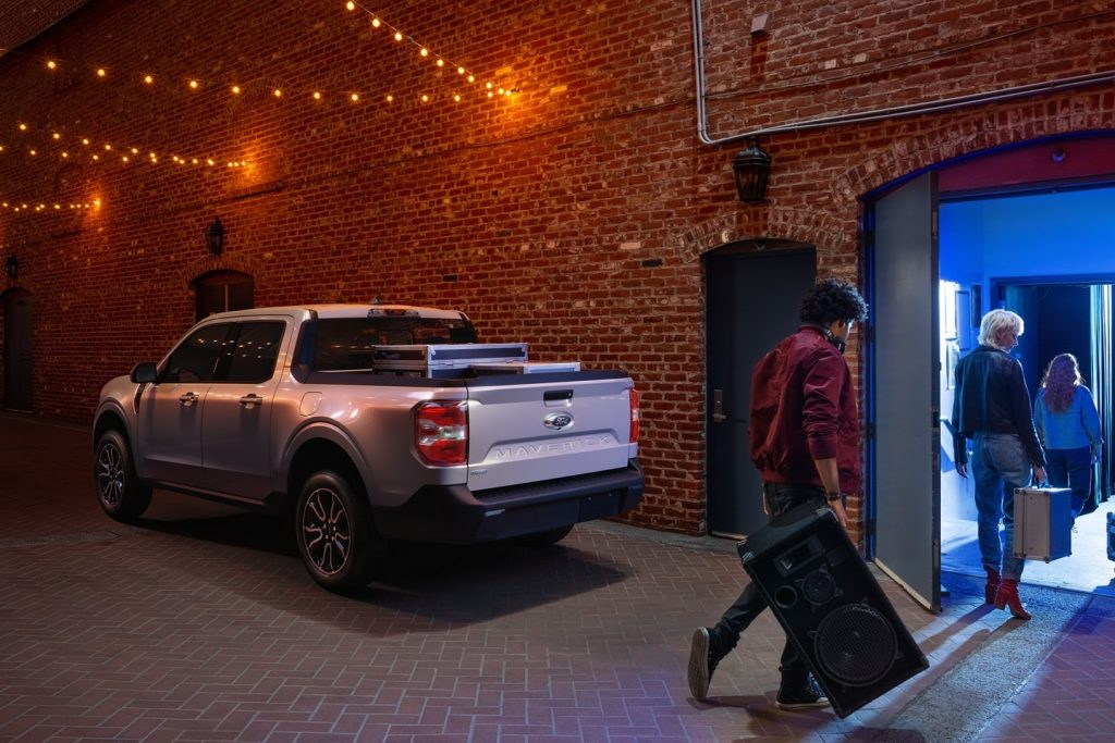A 2022 Ford Maverick compact pickup truck parked outside of a live music venue in an urban area