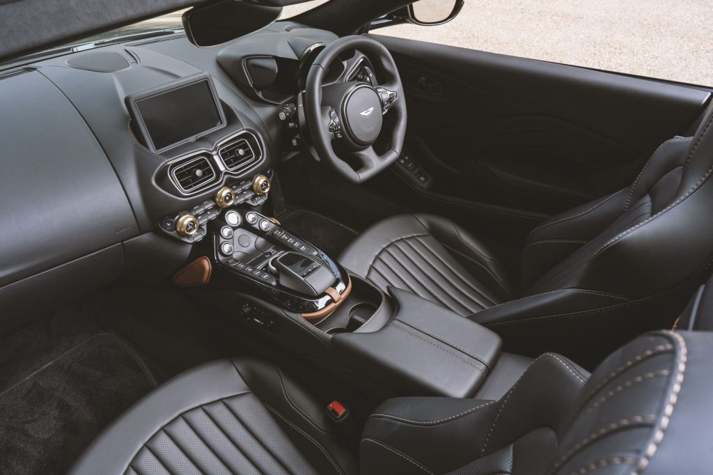 The black-and-brown leather seats and bronze-highlighted black dashboard of the A3-inspired Q by Aston Martin Vantage Roadster