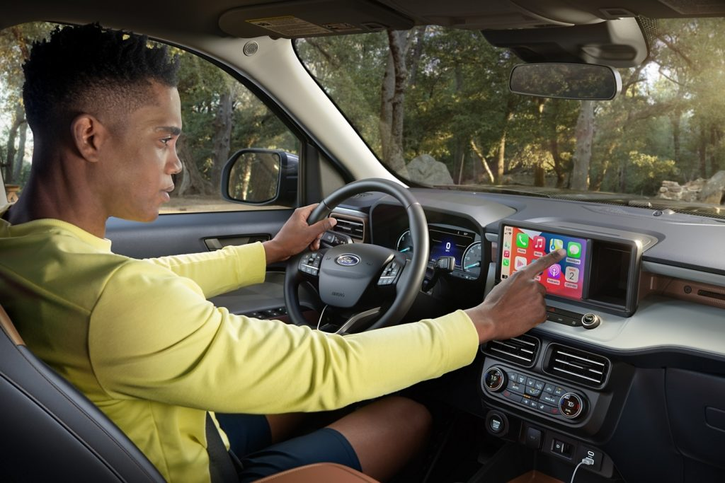 a driver uses the infotainment system of the 2022 Ford Maverick compact pickup truck