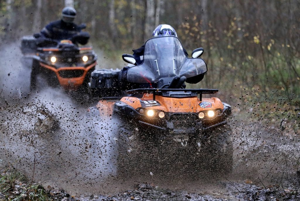 Two people in helmets ride orange ATVs through mud in a wooded area