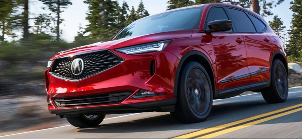 A red 2022 Acura MDX races down a wooded road.