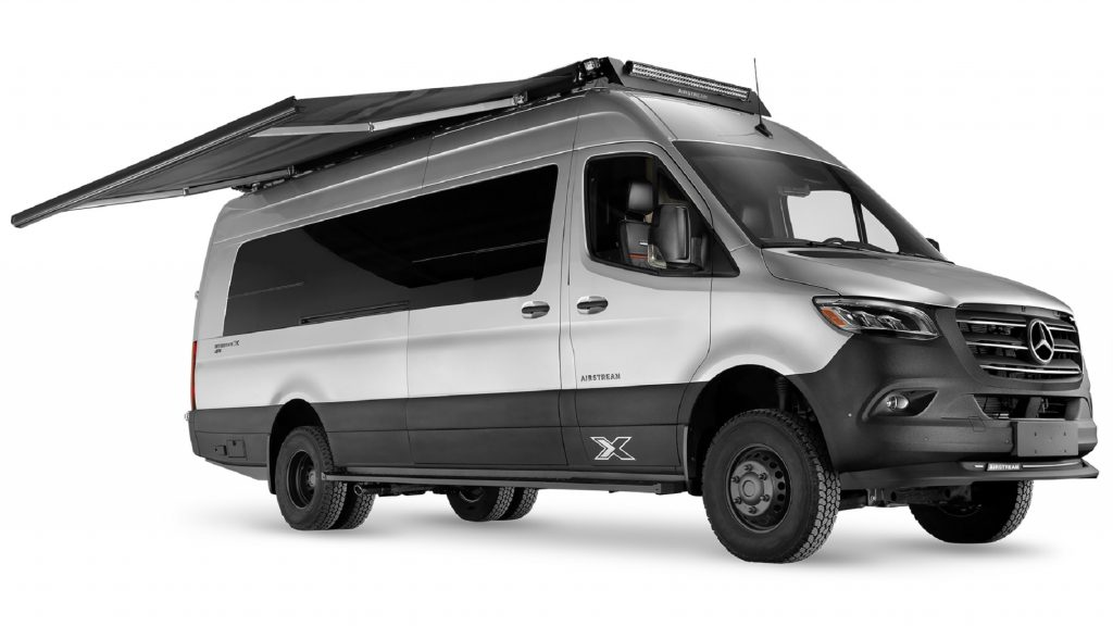 A silver-and-black Airstream Interstate 24X with its awning extended