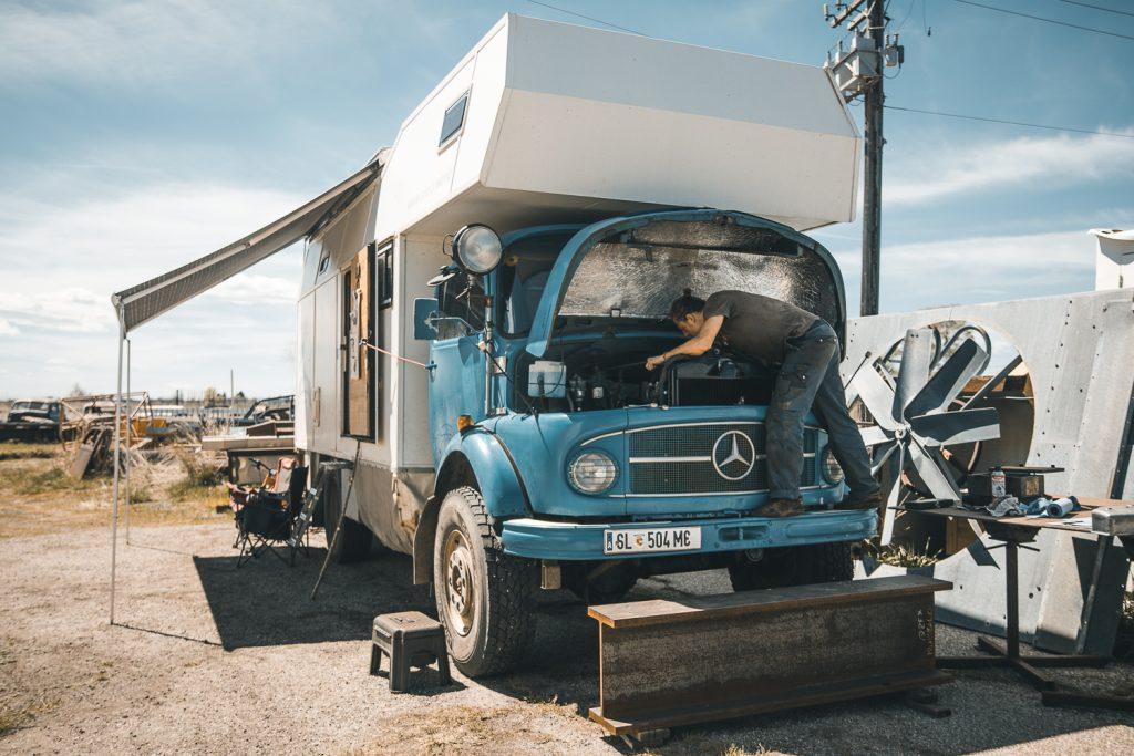 Man working on his vintage Mercedes camper van in the desert