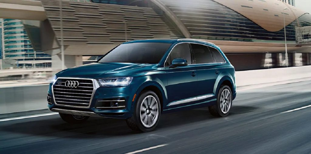 A blue 2021 Audi Q7 drives down the highway.