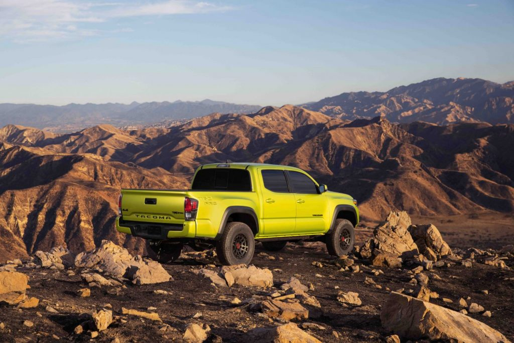 the electric green Toyota Tacoma TRD Pro color for 2022 perched on top of a Rocky Mountain
