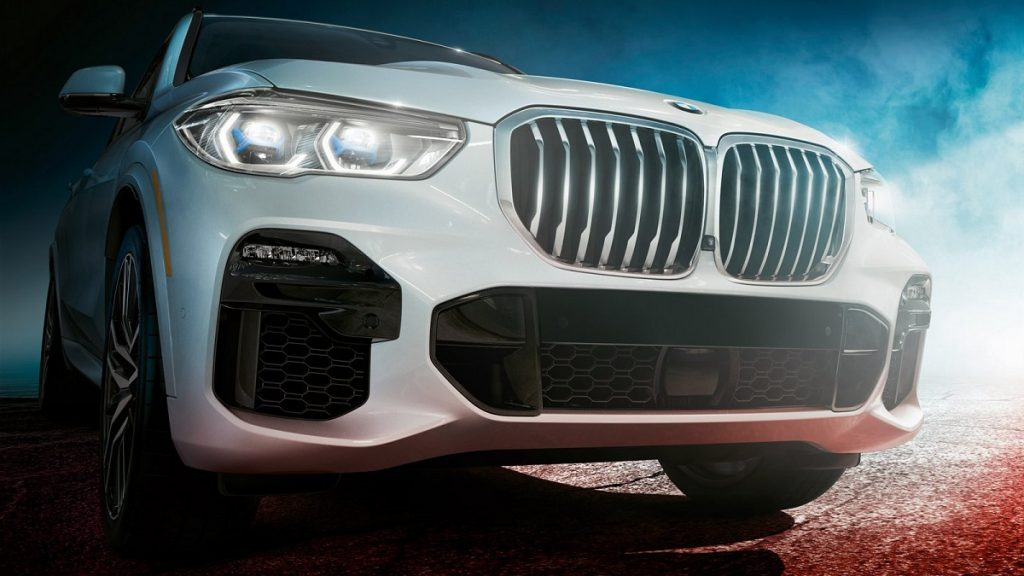 The front of a white 2021 BMW X5 at night.