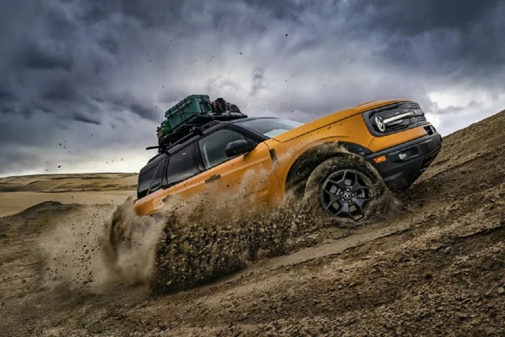 A yellow 2021 Ford Bronco Sport drives up a dirt hill.