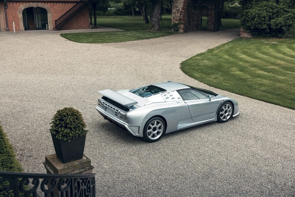 An overhead rear 3/4 view of a silver Bugatti EB110 SS on the grounds of a chateau