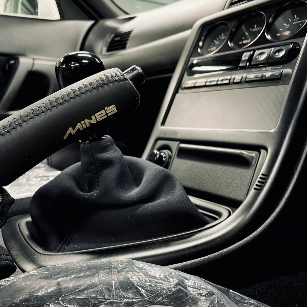 A close-up look at the Built by Legends Nissan R32 Skyline GT-R restomod's Mine's handbrake, shifter, and center console