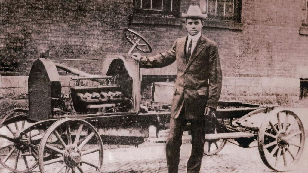 Charles Patterson standing in front of a C.R. and Sons car, the first Black-owned car company in the world