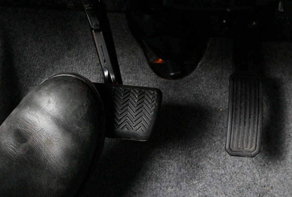 Someone pressing the brakes on a car, slamming on the brakes can cause damage to your car