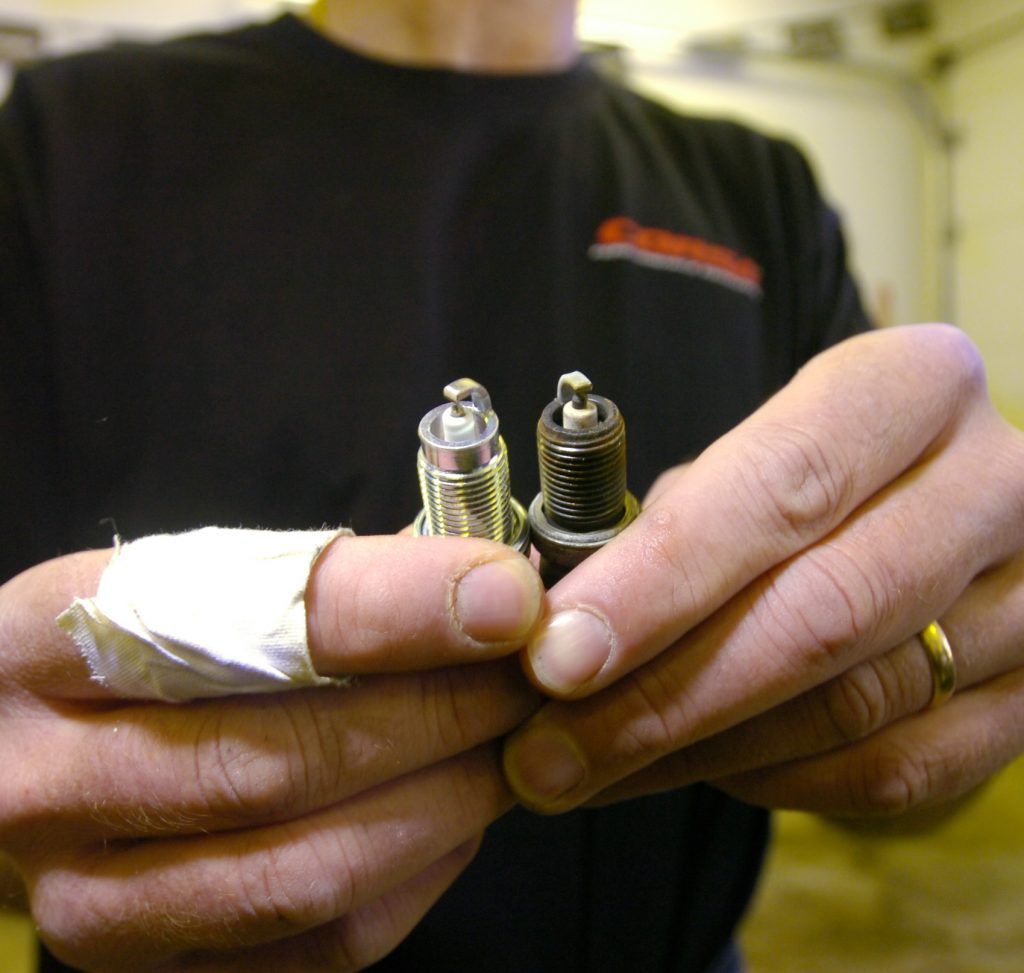 A black-shirted mechanic compares old and new spark plugs while changing them