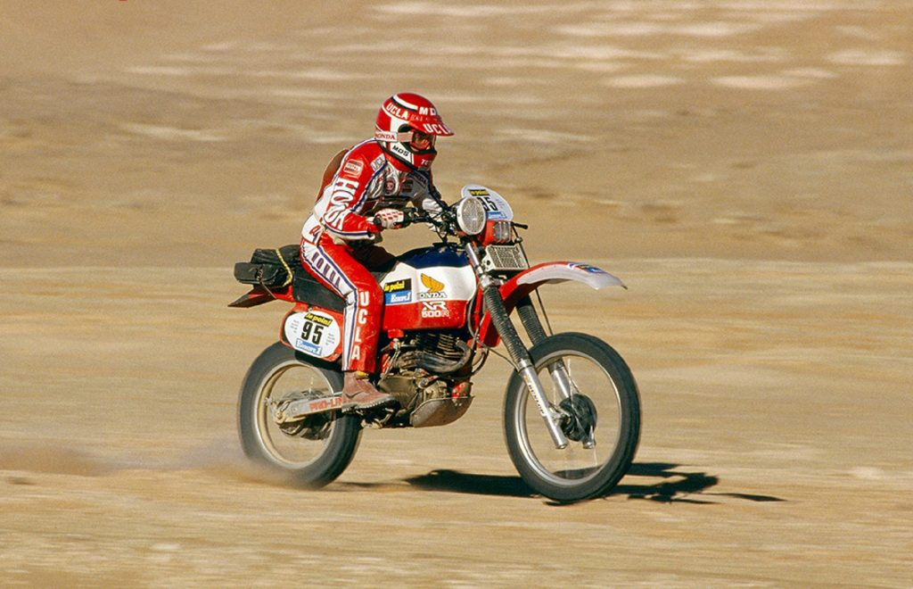 Red-clad Cyril Neveu on the red-and-white 1982 Honda XR500R Dakar Rally bike racing through the desert