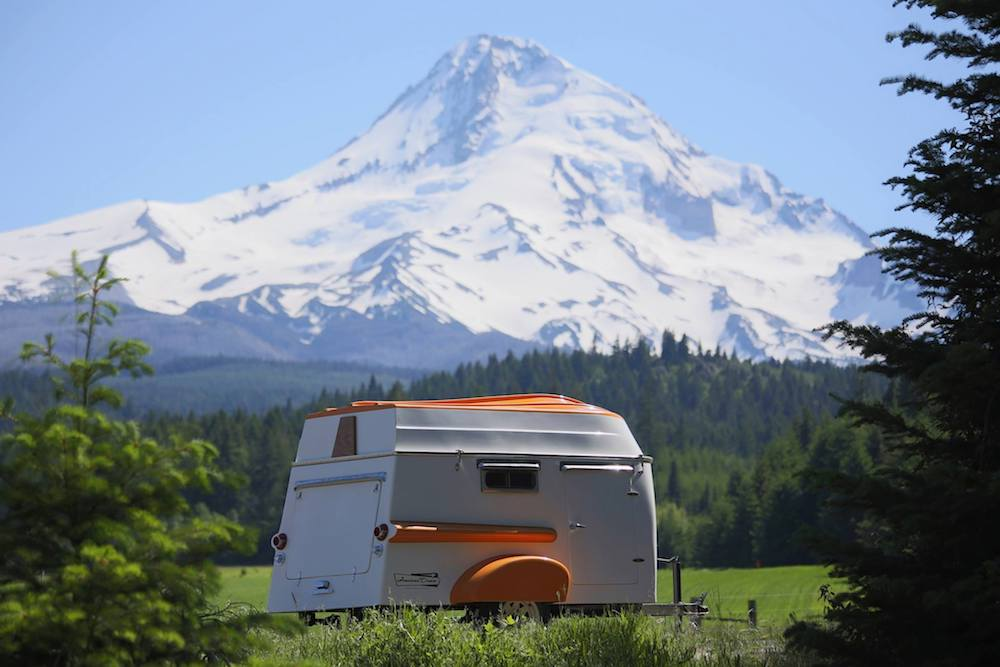 The American Dream trailer parked in a meadow with snowcapped mountains behind