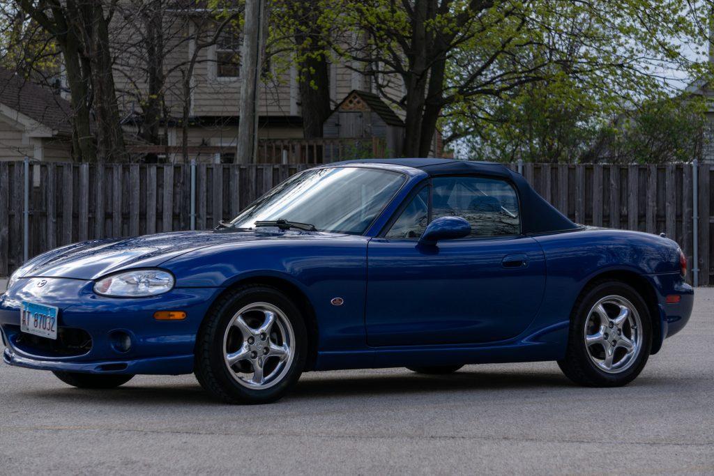 A blue 1999 Mazda MX-5 Miata 10th Anniversary Edition in a parking lot