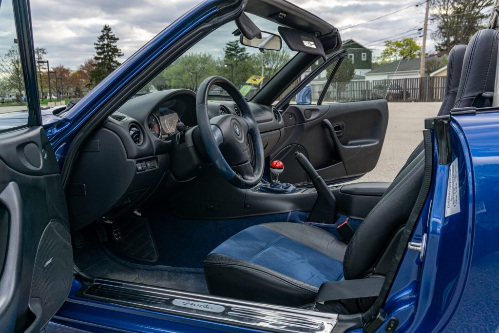 The blue-and-black interior of a blue 1999 Mazda MX-5 Miata 10th Anniversary Edition with its roof down