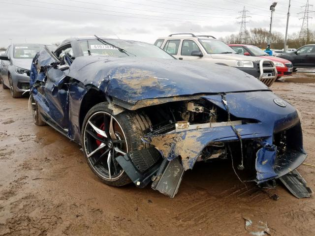 An image of a damaged Toyota Supra in an open lot.