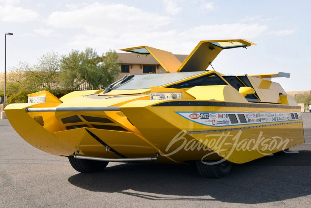 The yellow Dobbertin Hydrocar with its doors open parked in a parking lot