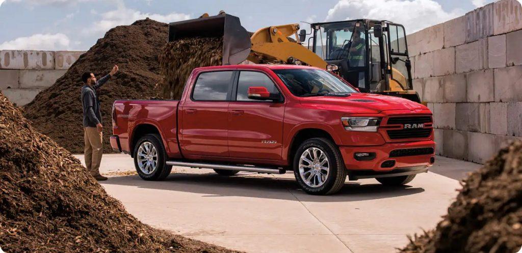 A red 2021 Dodge Ram between piles of dirt.