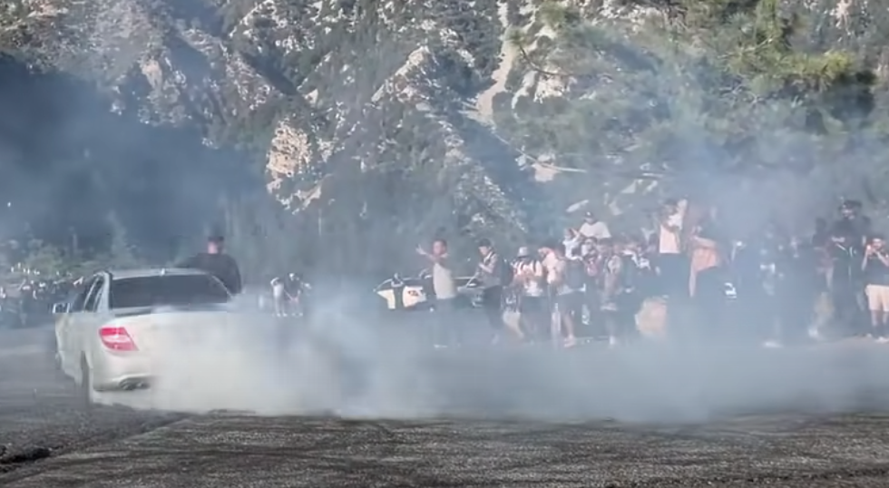 Complete idiots drifting Mercedes sedan in a crowd