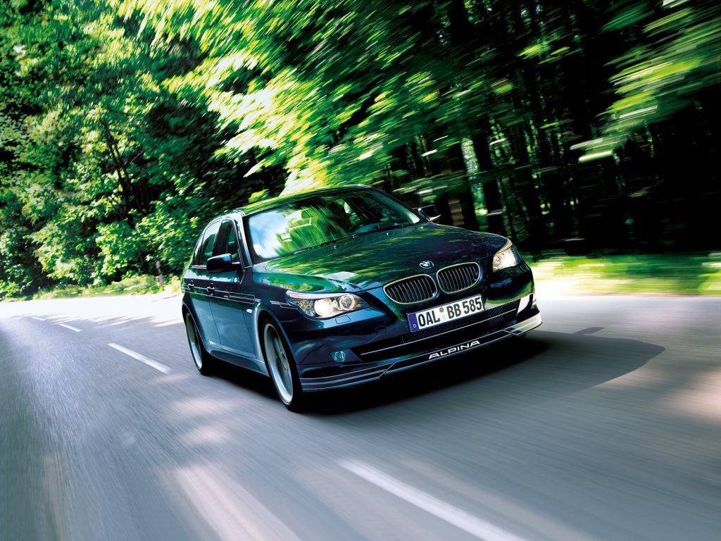 A black E60 BMW Alpina B5 S drives down a forest-lined road