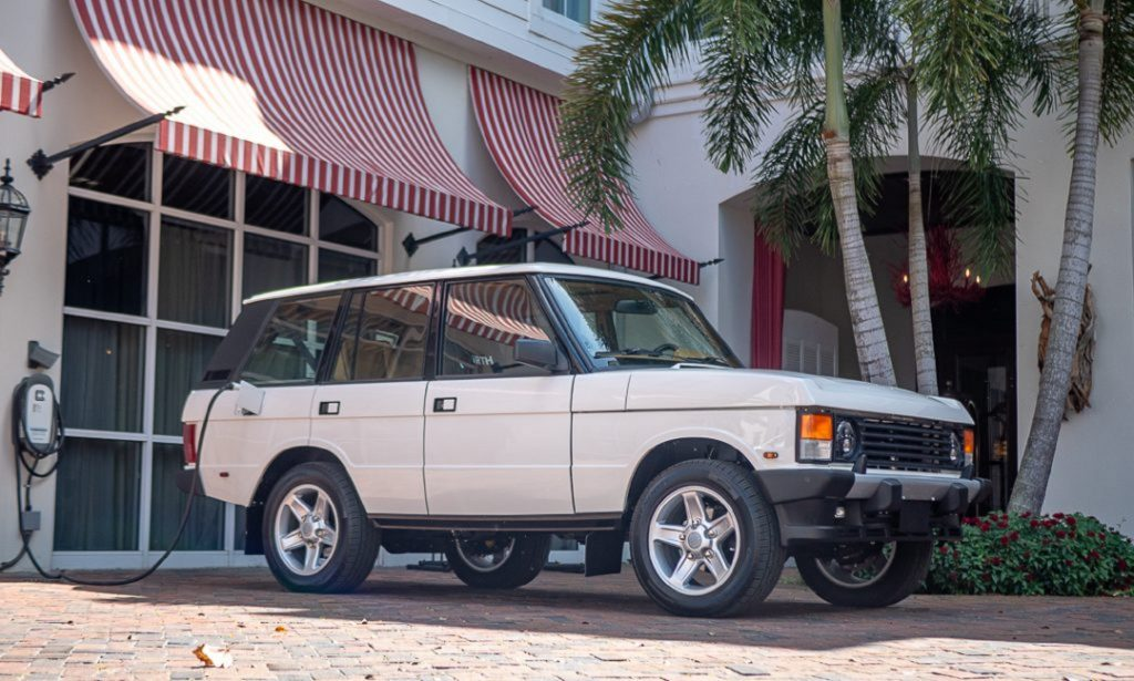 The white ECD Automotive Design electric Range Rover Classic plugged into a charger by a white building