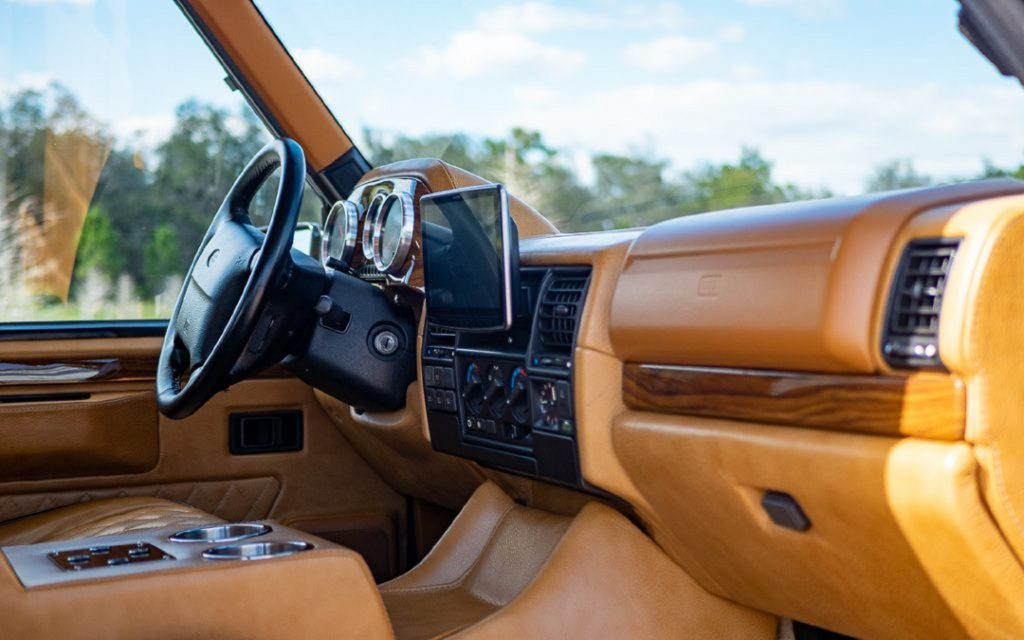 The tan-leather-upholstered front seats and leather-and-wood-trimmed dash of the ECD electric Range Rover Classic