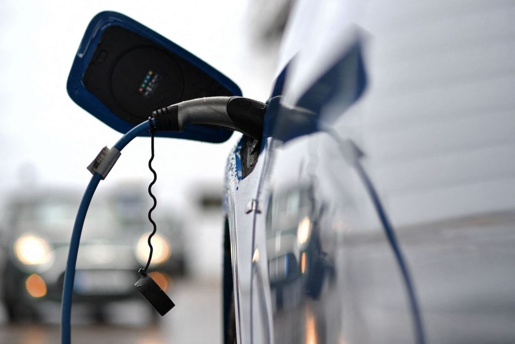 A blue EV being charged at a charging station