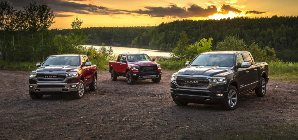 three ecodiesel 2021 ram 1500 models in gravel near a wooded lakeshore.
