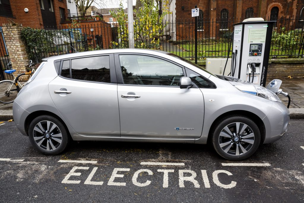 A silver Nissan Leaf EV charging